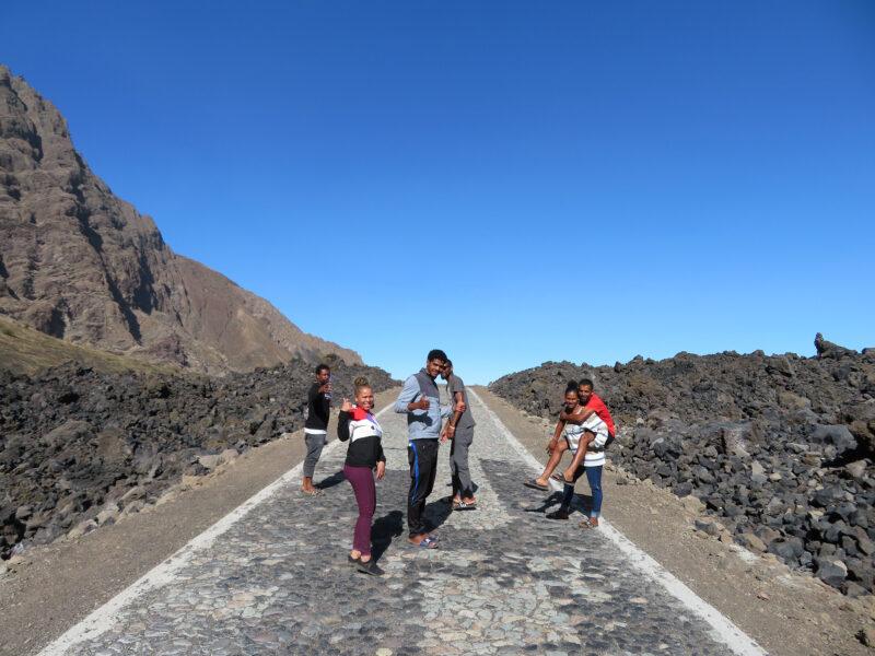 Jovens protagonistas sorriem para a câmara enquanto parecem aguardar no meio de uma estrada que parece subir. A paisagem é composta por areia vulcânica cujas tonalidades escuras contrastam com o céu azul