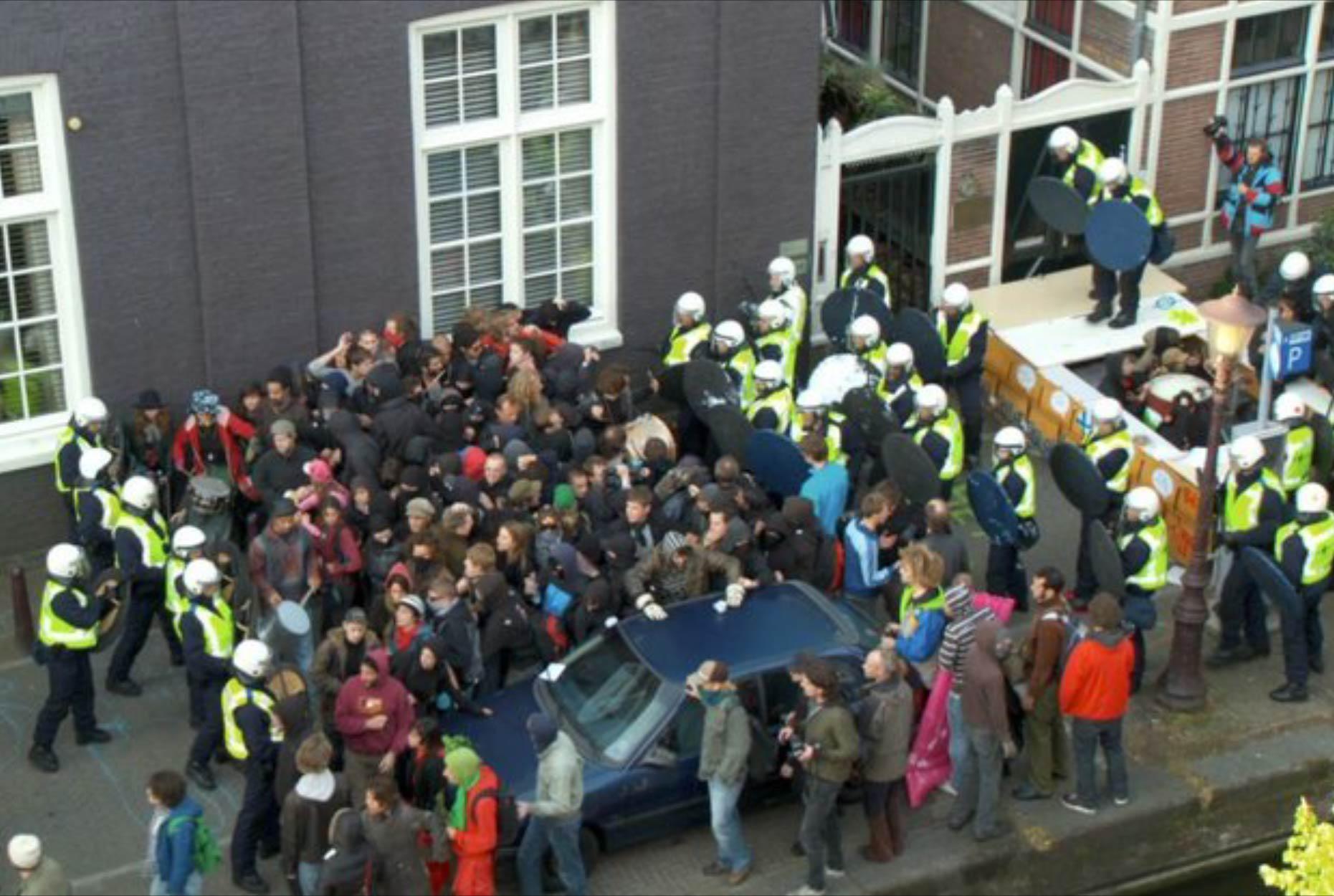 Polícia cerca manifestantes em rua estreita. Alguns manifestantes levantam as mãos como que em rendição.